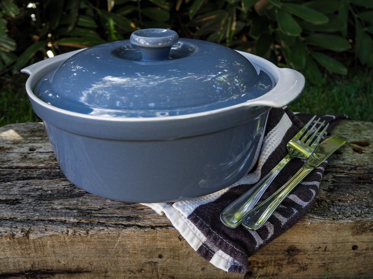 Casserole dish with teatowel and cutlery
