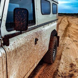 Dirty Land Rover County on beach at Exmouth