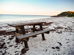 Wooden picnic table and chairs on beach at Milligan Island