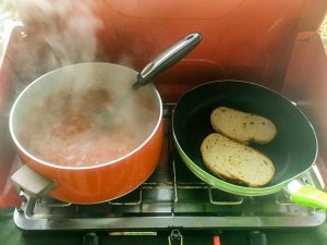 Beans and bread cooking on camp stove